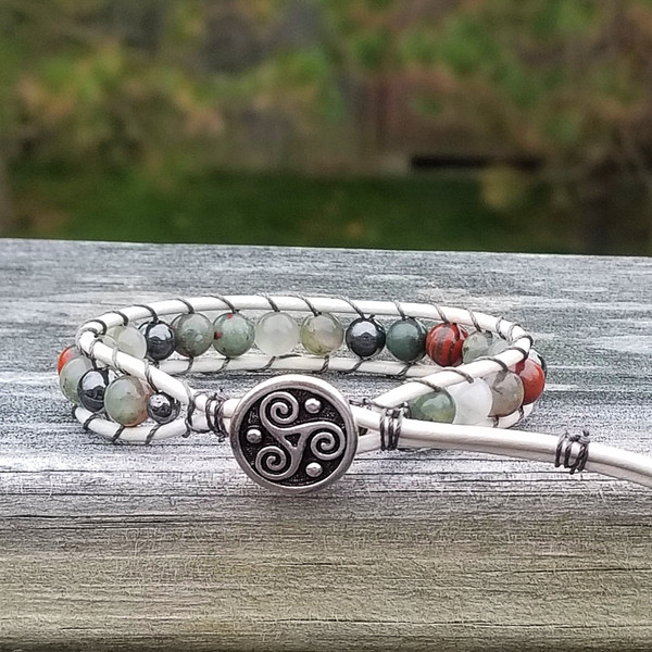 White leather with African Blood Stone & Hematite beads. Pewter Triskele button closes bracelet. Two button holes fits 6 1/4 inch & 7 1/4 inch wrist.