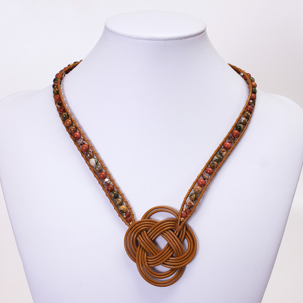 Tan leather necklace featuring double coin knot design in the center with Rhyolite, Brown Goldstone and Swarovski crystals interwoven up the sides of the necklace. Gold plated lobster clasp and links makes the  length adjustable.