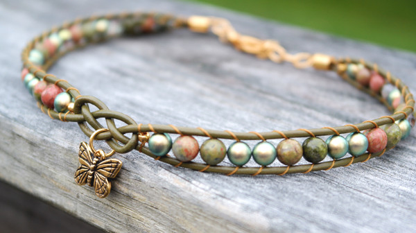 Ukanite stones, Swavorski Pearls and Crystals threaded onto olive green leather. Leather features a focal celtic design and gold plated butterfly charm. Gold plated lobster clasp and jump rings make this choker adjustable to size.