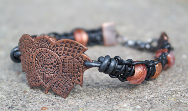 This remarkable bracelet will get noticed! Unique copper focal point framed with gun metal leather cords knotted with copper beads and roller beads. Gun metal lobster clasp and jump rings create and adjustable fit.