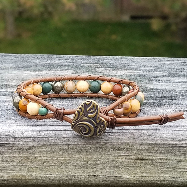 Brown leather bracelet with Red Creek Jasper & Pyrite beads. Closes with Antique Brass Amor Button. Two button hole closure fits 6 in & 6 3/4 in wrist.