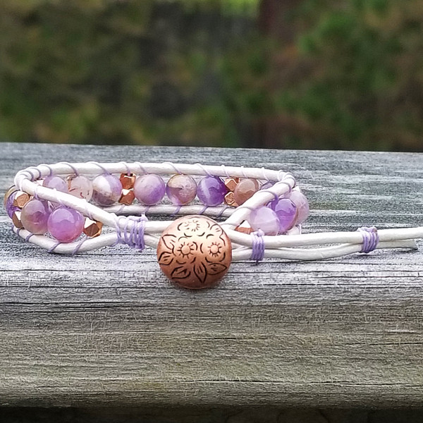 White leather with Lt Amethyst and Copper beads. Copper button for the two button closure. Fits wrist size 5 3/4 inch & 6 3/4 inch.