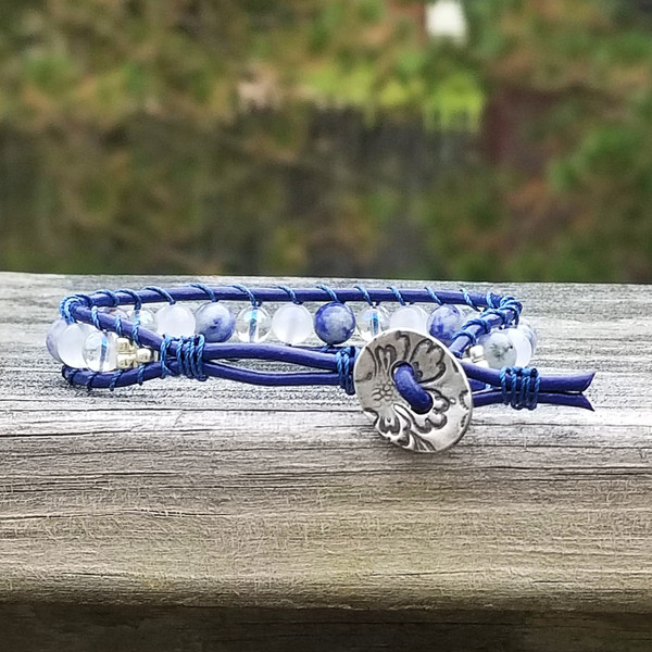 Blue leather with Solidite, Snow Quartz and Clear Quartz (coated) beads. Pewter Jardin button closure. Two button hole fits 6 inch & 6 3/4 inch wrist