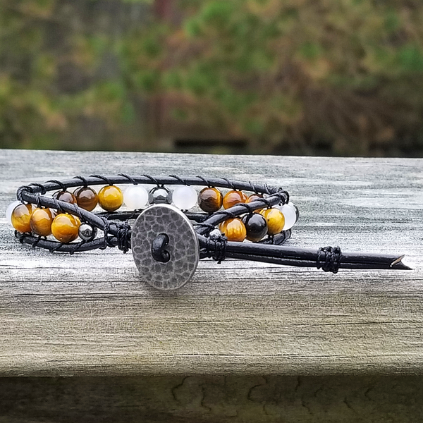 Black leather with Tiger Eye, Snow Quartz, and Hematite Beads. Hammered Pewter button closure. Two button hole fits 6 inch & 7 inch wrist