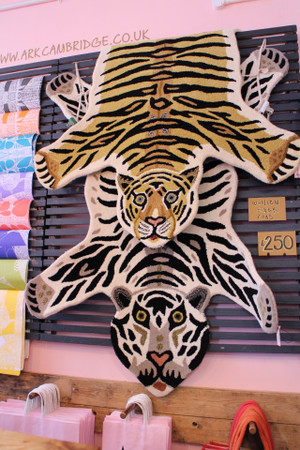 Tiger rugs insitu on our wall in the shop