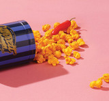 Overhead view of Spicy CheeseCorn with flavor cues and a spilled Petite Signature Blue Tin
