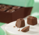Hover - Profile view of Milk Mint chocolate piece cut in half with box of chocolates in the background