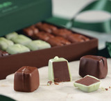 Hover - Profile view of Mint Trio chocolate pieces cut in half with box of chocolates in the background