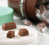 Hover - Profile view of Milk Mint chocolate piece cut in half with round of Milk Mint in the background