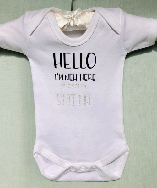 Welcome the newborn baby into the world with this gorgeous personalised babysuite HELLO I'M NEW HERE #team  A perfect present for expectant or new parents.  It can make a lovely keepsake as it can be personalised with any surname up to 12 characters.