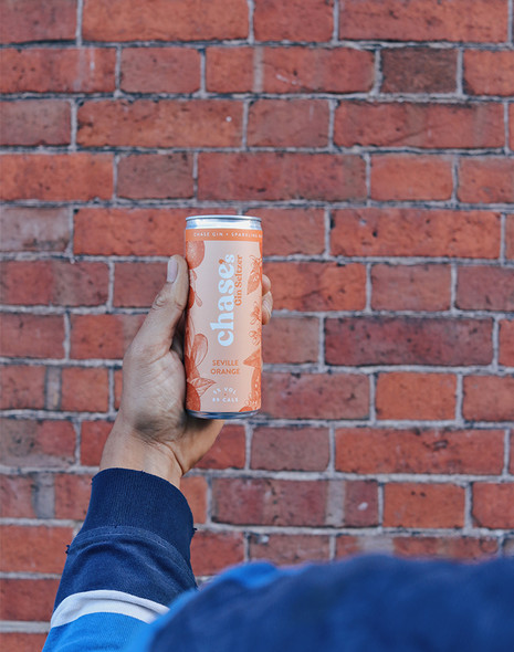 Holding a can of Chase Gin Seltzer in Seville Orange flavour