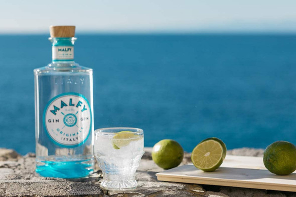 Malfy Originale Italian Gin, 70CL served chilled with plenty of ice and a slice of lemon against a sunny Italian sea backdrop