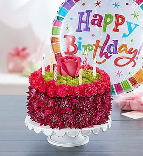 EXCLUSIVE Purple adds a pop with this Birthday Wishes Flower Cake. Handcrafted with fresh carnations, mums, and poms in shades of purple, pink, and green, it's a  centerpiece for a celebration. Want to make the day even more special? A birthday balloon will take the fun to new heights!