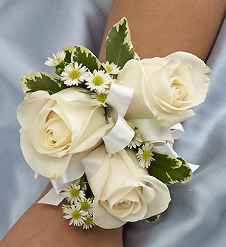 White Corsage Elegant white roses, white Monte casino and variegated pittosporum laced with white ribbon creates an elegant accompaniment for the mother of the bride or groom, grandmothers, or treasured relatives.