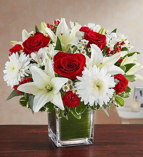 cube glass vase with assortment of white lilies, and red roses.