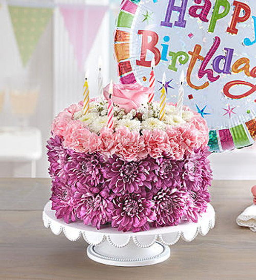 Birthday Wishes Flower Cake Pastel EXCLUSIVE No matter how you slice it, our Birthday Wishes Flower Cake will make their day! Handcrafted from carnations and poms in soft hues of pink, lavender, and white, it's a one-of-a-kind centerpiece for a memorable celebration. Want to make the day even more special? A birthday balloon will take the fun to new heights!