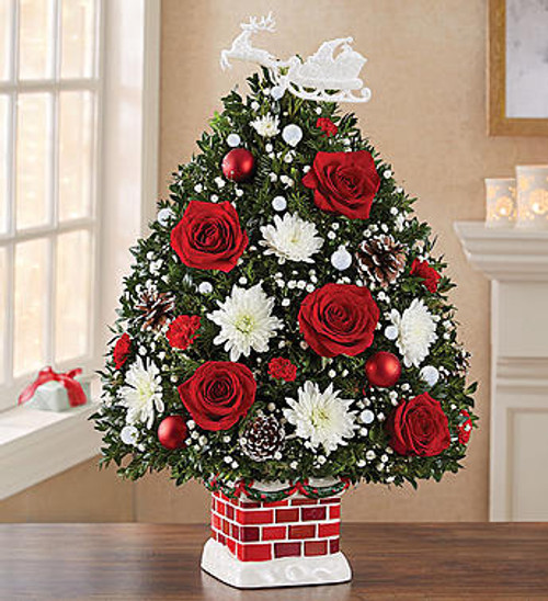 EXCLUSIVE The stockings are hung by the chimney with care. Here's one more special gift to share! Our limited-edition Night Before Christmas Holiday Flower Tree beautifully captures the anticipation of Santa's arrival. Trimmed in red & white blooms, this truly original evergreen arrangement arrives in our exclusive new ceramic chimney container. With its snowy detail and old-world charm, this keepsake design includes a nostalgic ornament of Old Saint Nick and his sleigh, bringing joy to family & friends while becoming a treasured part of their holiday traditions.