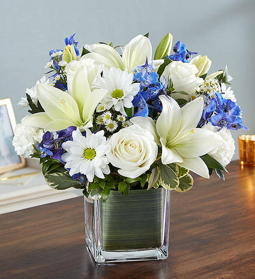 Soothe their tears as they mourn the loss of a loved one with the serenity of blue and white. Our sympathy arrangement of fresh blue delphinium, white roses and lilies, expertly gathered together in a clear glass cube lined with Ti leaf ribbon, makes for an exquisite gesture of comfort and healing.