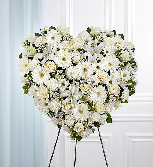 All-white heart-shaped arrangement of roses, hybrid lilies, Gerbera daisies, carnations, daisy poms, waxflower and monte casino; accented with baby's breath and soft, lush greenery