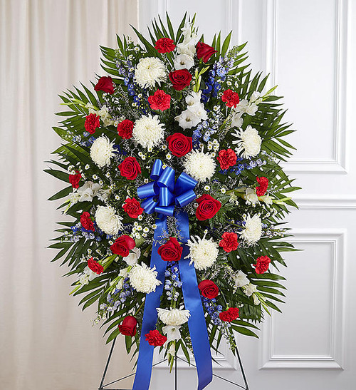 They served their country with honor and pride, which is how they should be remembered. Our patriotic standing spray arrangement is meticulously handcrafted by our expert florists to honor a brave veteran who has passed away. Filled with fresh blooms in red, white and blue for a lush, full presentation, it's a proud and fitting final tribute.