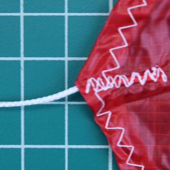 Close up showing stitching, a shroud line and the hem of the 1.1 oz parachute from Top Flight Recovery.