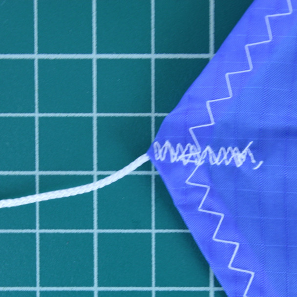 Close up of the 1.7 oz parachute from Top Flight Recovery showing stitching, a shroud line and the hem of the product.