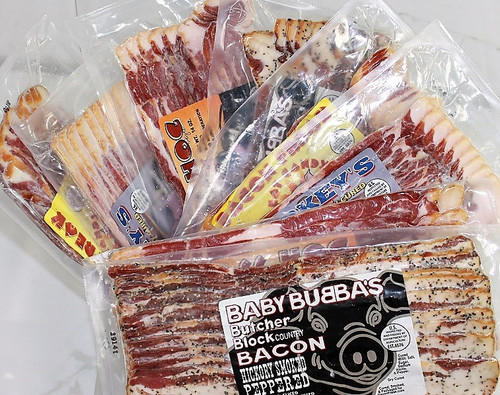 8 packages of dry cured bacon including two packs each of: Baby Bubba's Butcher Block Peppered Bacon, Bacon Freak Apple Wood Smoked Bacon, Boss Hog Hickory Smoked Bacon, Smokey's Maple Wood Smoked Bacon