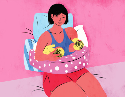 Mother breastfeeding twins with pillows