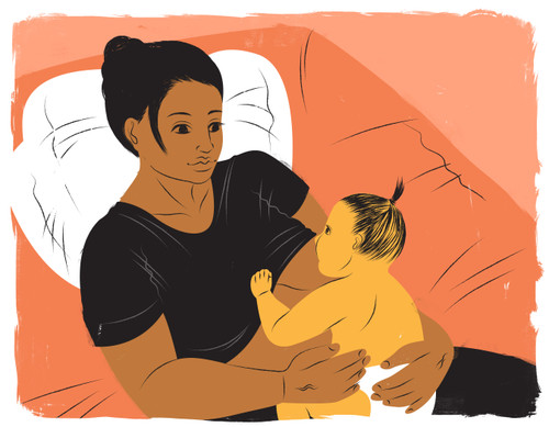 Mother breastfeeding in bed with orange sheets