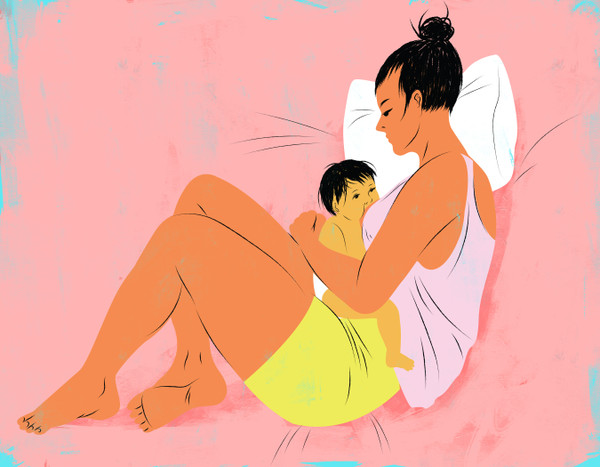 Mother curled up with breastfeeding baby