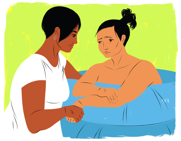 Doula holding mother's hand during water birth