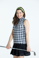 Smiling woman golfer wearing a buffalo check Keep it Covered sleeveless top and a black Pleated to Play golf skort