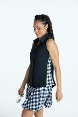 Woman wearing a black sleeveless Slimming Splouse golf top and a buffalo check Pleated to Play golf skort