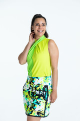 Smiling woman wearing a grass green Twist and Shout sleeveless golf shirt and a splatter print My Go To golf skort