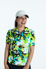 Smiling woman golfer wearing a splatter print Keep it Covered shortsleeve golf top, a black/white Wrap it Up golf skort, and a We've Got You Covered hat