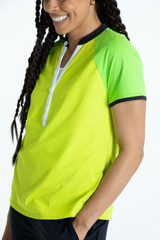 Smiling woman golfer wearing a chartreuse yellow Swing for the Fences shortseleeve golf shirt