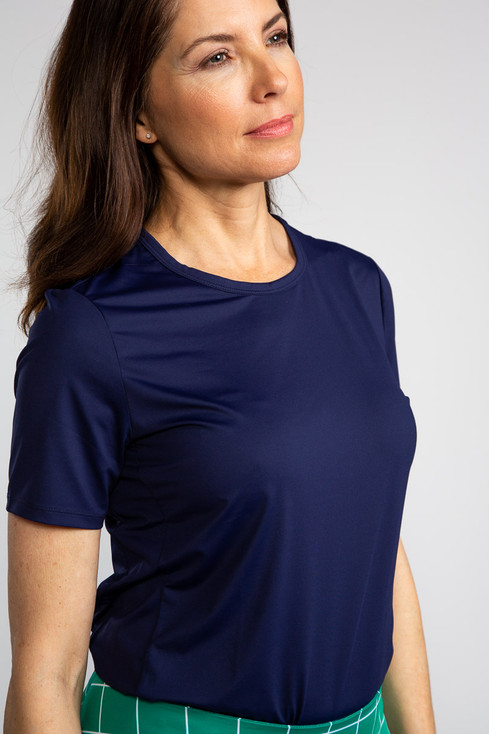 Woman in navy blue Tee It Up shortsleeve golf shirt