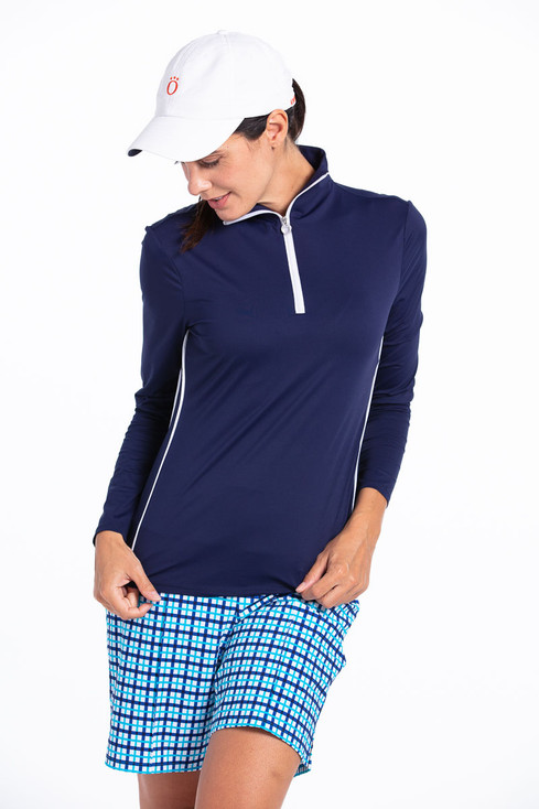 women golfer looking down wearing a navy longsleeve golf shirt, blue check shorts and a white golf hat.