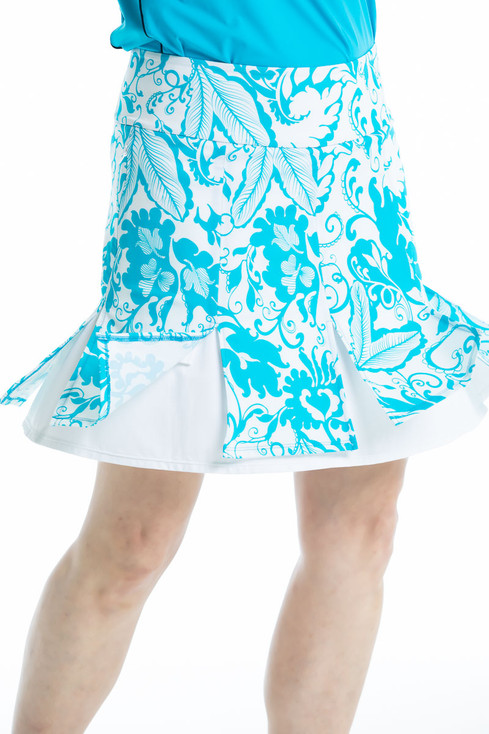 women wearing a bright blue and white floral golf skort and spinning to reveal the white under layer.