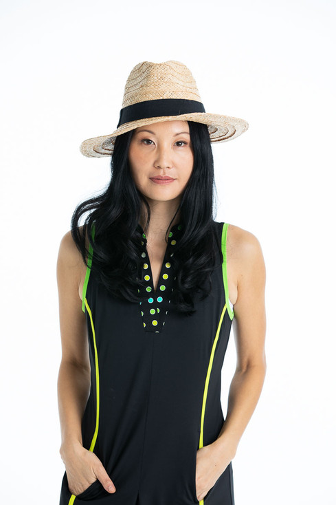 women with hands in pockets wearing sleeveless black golf dress and straw hat