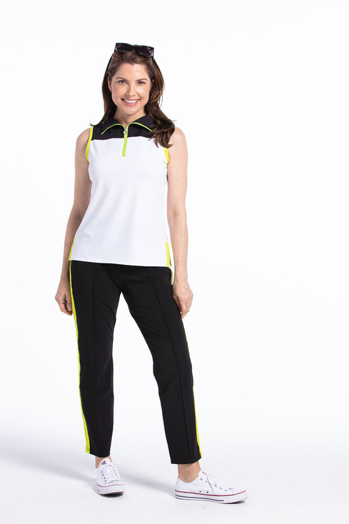 women golfer in white and black sleeveless golf top and black pants smiling