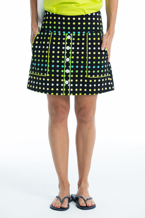 women golfer with hands in pockets  wearing black polka dot skort with