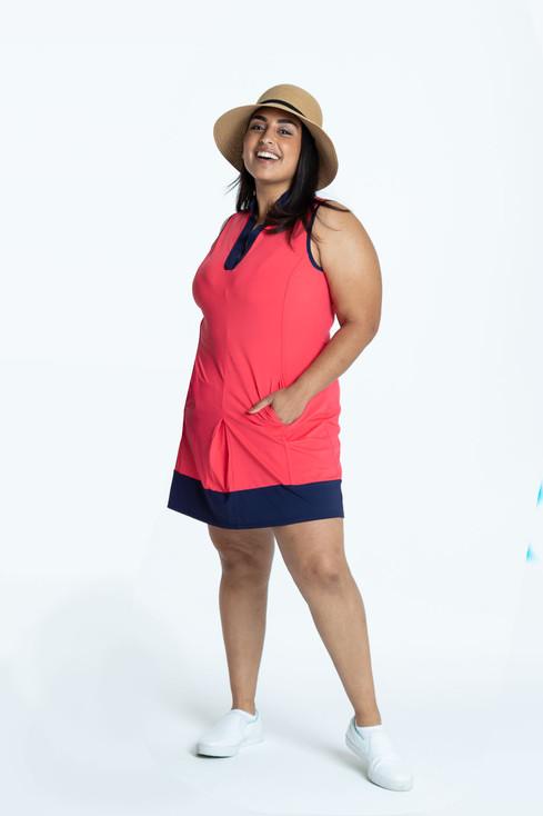 Woman wearing a watermelon red Kick Pleat Chick sleeveless golf dress