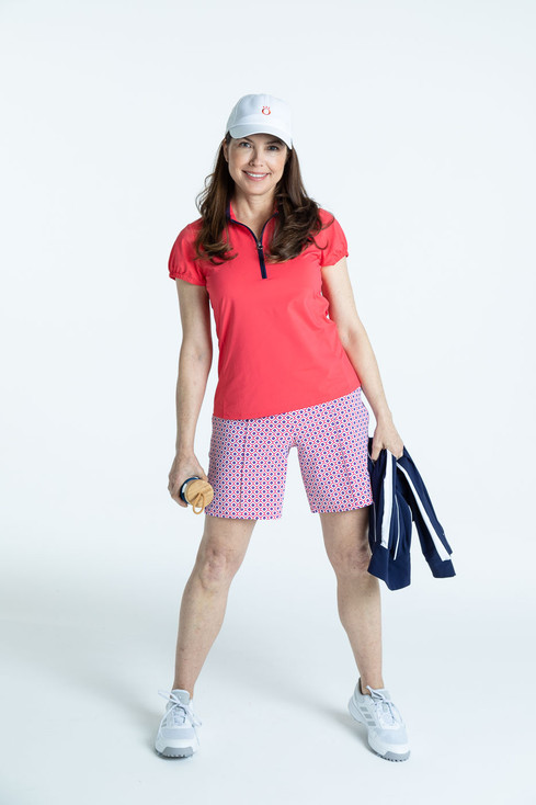 Woman golfer in a watermelon red Prettier Than a Polo shortsleeve shirt,  Tailored Track Trousers in Foulard print, and a white We've Got You Covered hat