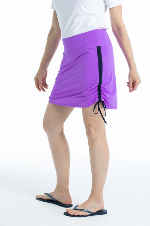 Side view of woman in Rouched and Ready golf skort - lilac purple with a white shortsleeve To a Tee t-shirt