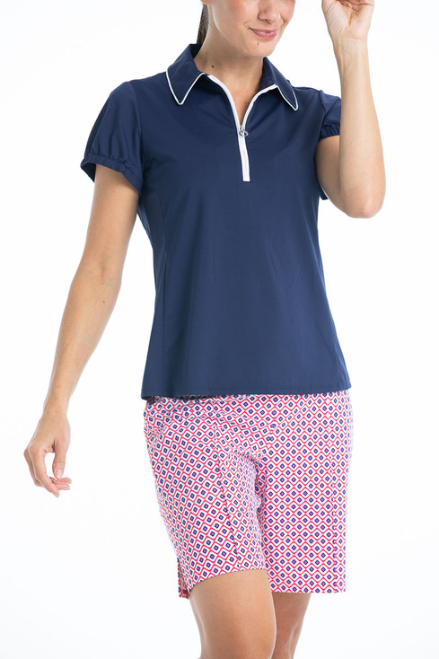 Woman in Tailored and Trim golf shorts - Foulard print and a navy blue Prettier Than A Polo shortsleeve golf shirt
