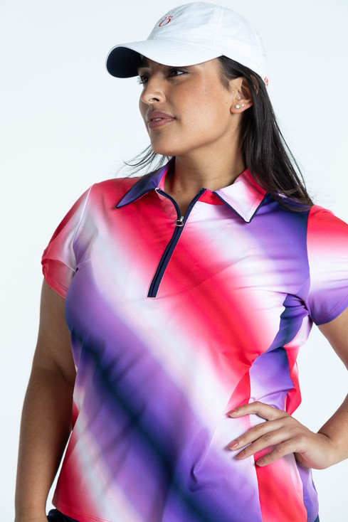 Woman golfer wearing an ombre Prettier Than A Polo shortsleeve golf shirt and a white We've Got You Covered hat