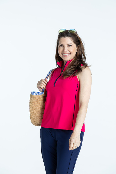 Smiling woman golfer in raspberry red Keep it Covered sleeveless golf top and navy blue Smooth Your Waist Golf Crop Pants