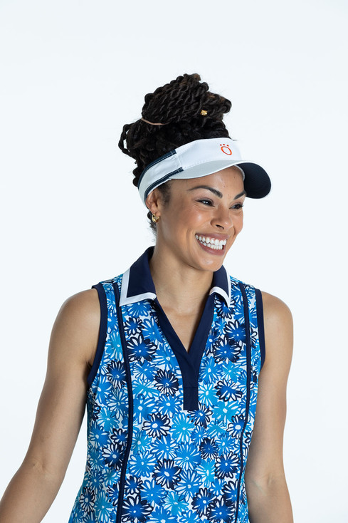 Smiling woman golfer in a crazy daisy Shape Shifter sleeveless golf top and a white No Hat Hair Visor