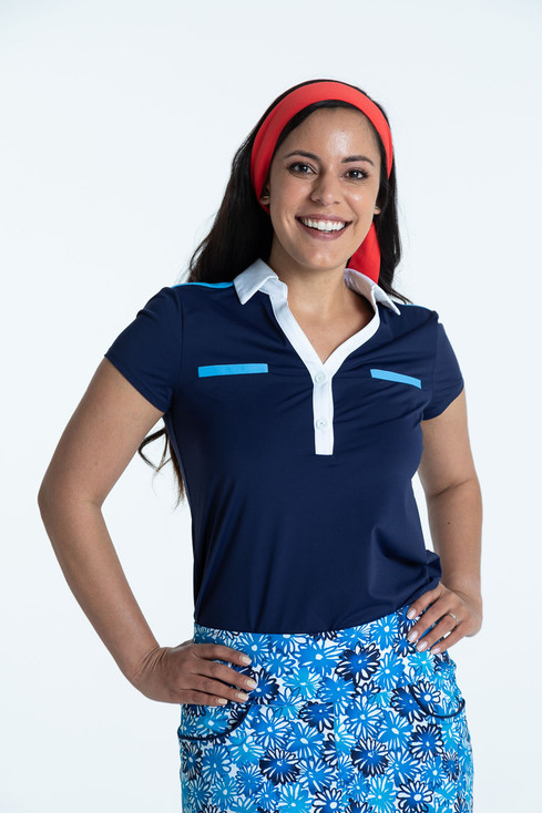 Woman golfer in navy blue Shoulder Opener Shortsleeve Golf Top and crazy daisy Fit and Flare Golf Skort.